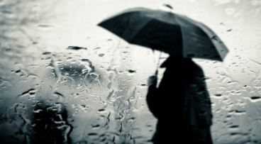 A-man-standing-outside-in-the-rain-with-an-umbrella_5120x2880.jpg